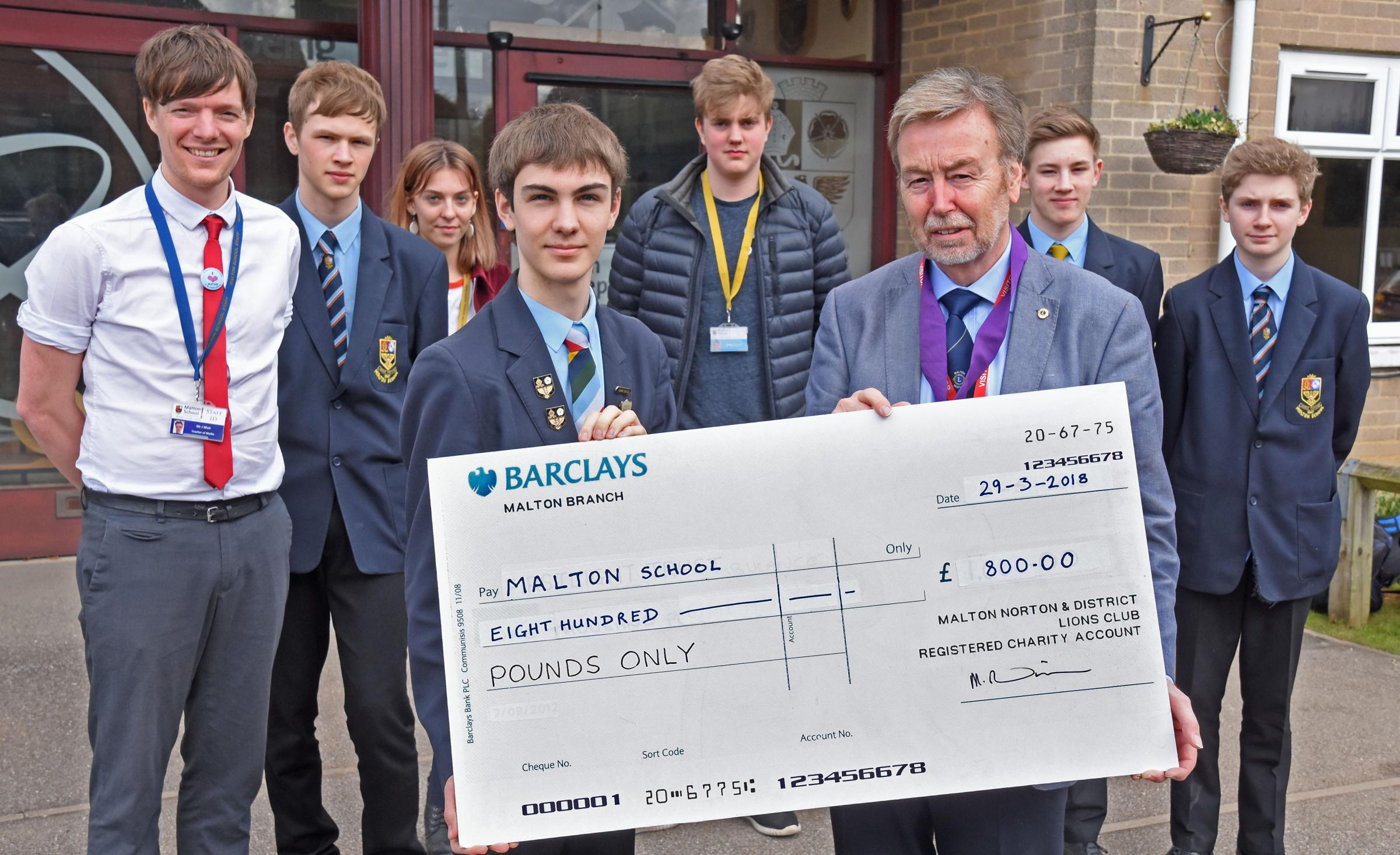 Steve Sidaway, right, vice-president of Malton Lions, presents a cheque to pupils at Malton School who are going on a Camp International trip, watched by teacher James Muir, left, who will be leading the trip   Picture: Nigel Holland