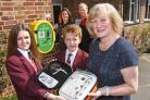Sue Parsons, mother of the late Tom Parsons, hands over a new defibrillator to Norton College pupils Bailey Downes and Liam Barrett, watched by teachers Laura Olley and Sam Triffitt     Picture: David Harrison