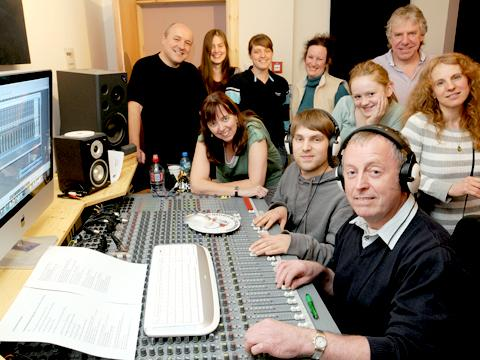 Rob Davies (foreground) and Sam Holdstock, of Melrose Yard Studios, at the mixing desk, with the musicians involved in recording the charity song