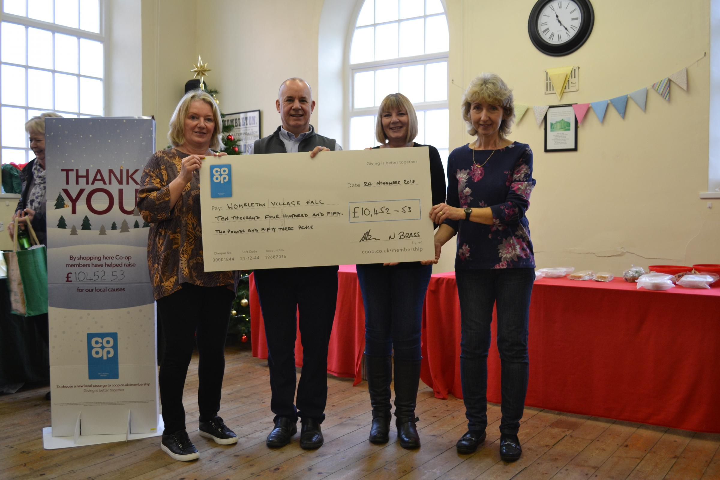 Nigel Brass, centre, manager of the Co-op in Kirkbymoorside, hands over a cheque for just over £10,000 to Louise Slater, Shirley Turnbull and Sheran Monkman, Wombleton Village Hall committee members