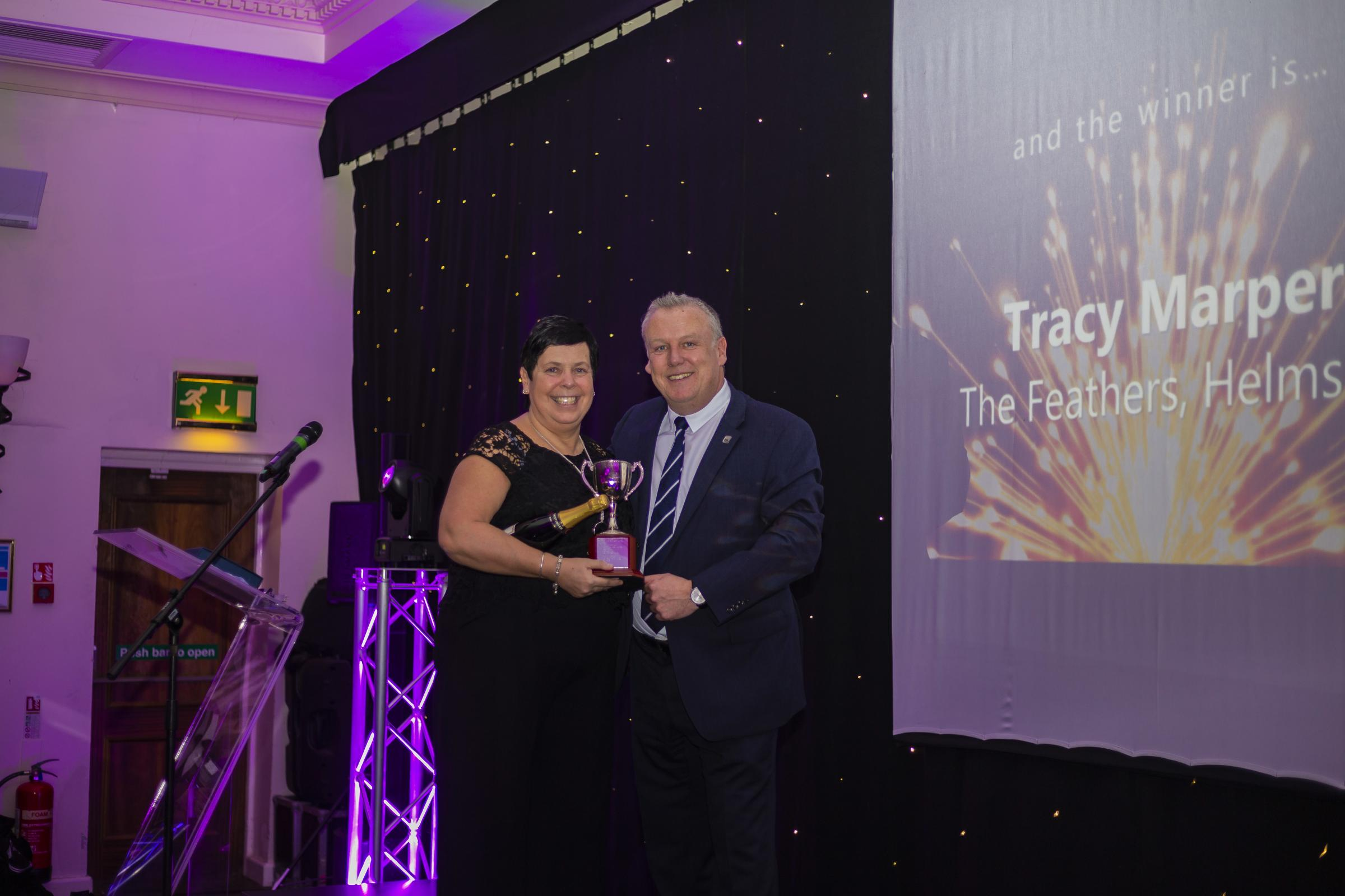 Tracy Marper, general manager of the Feathers Helmsley, picking up her award from David Campbell, head of operations for The Coaching Inn Group